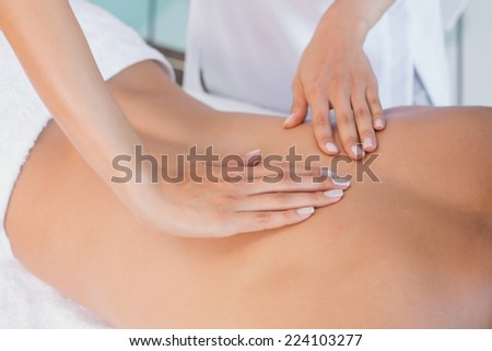 Close up mid section of a man receiving back massage at spa center