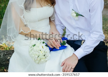 Close-up mid section of a newlywed couple with wedding rings and bouquet