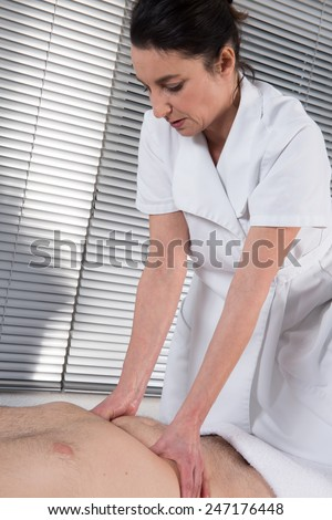 Close-up mid section of a physiotherapist massaging man's body