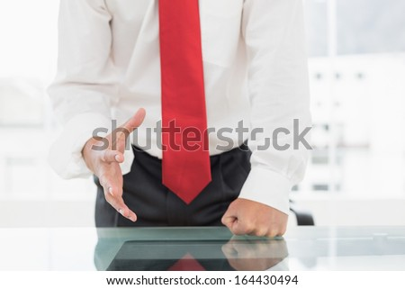 Close-up mid section of a well dressed businessman with clenched fist on the desk at office - stock photo