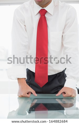 Close-up mid section of a well dressed businessman with clenched fists on the desk at office - stock photo