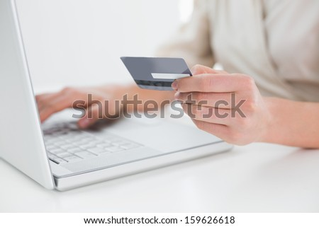 Close-up mid section of a woman doing online shopping through laptop and credit card - stock photo