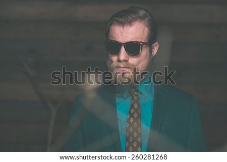 Close up Middle Age Man with Beard and Mustache Wearing Elegant Formal Fashion with Sunglasses on Wooden Wall Background. - stock photo