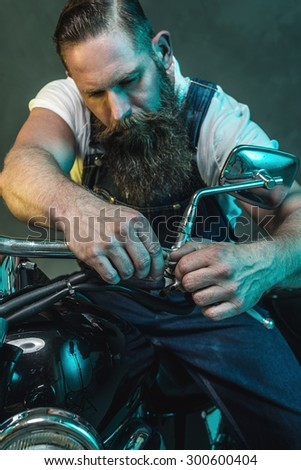 Close up Middle Aged Bearded Man in Denim Jumpsuit Fixing Something In Front of his Motorcycle Against Black Smoky Wall Background. - stock photo