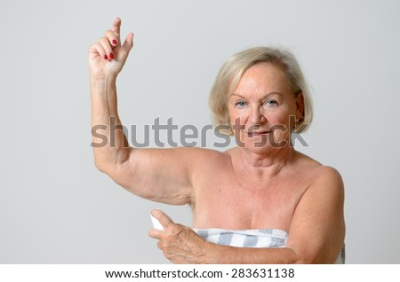 Close up Middle Aged Blond Lady Applying Deodorant on Armpit After Shower While Looking at the Camera Against Light Gray Wall. - stock photo