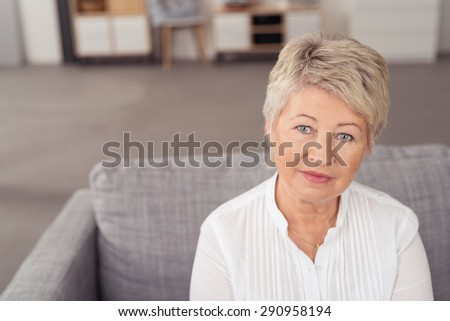 Close up Middle Aged Blond Woman Sitting on Gray Couch While Looking at the Camera