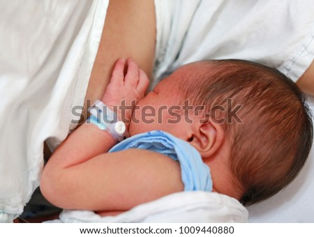 Close up mother breast feeding her newborn child.