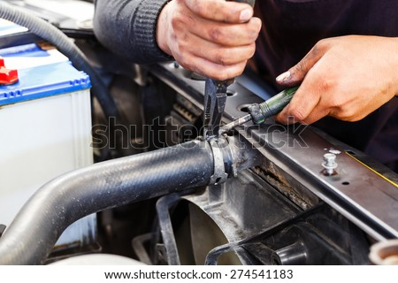Close up motor vehicle mechanic repairing car radiator, automotive maintenance service