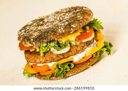 Close up Mouth Watering American Burger with Patty, Cheese and Fresh Veggies, Isolated on a Beige Background. - stock photo