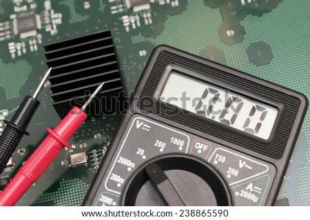 Close-up multimeter on PCB plate. - stock photo