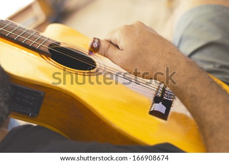 Close-up - musician playing acoustic guitar - man's hand - stock photo