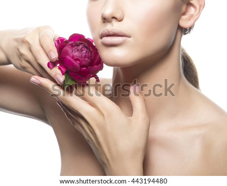 Close-up natural lips and open shoulders of caucasian brunette young woman posing with peony flower in hands. Studio portrait. Isolated on white background.  - stock photo
