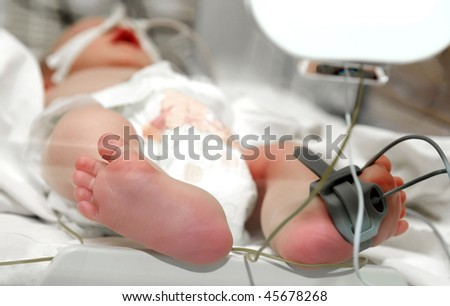 close-up newborn baby foot in infant incubator - stock photo