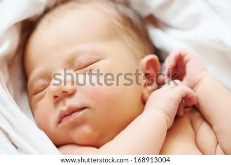 Close-up newborn baby sleeping in white bedsheet - stock photo