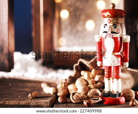 Close up Nutcracker Toy and Nuts on Wooden Table Near Window Pane. Captured on Christmas Holiday Season. - stock photo