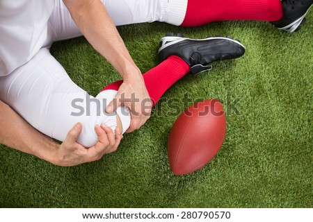 Close-up Of A American Football Player With Injury In Leg On Field - stock photo
