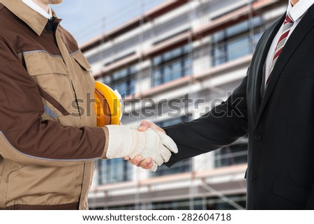 Close-up Of A Architect Wearing Glove Shaking Hand With Businessman - stock photo