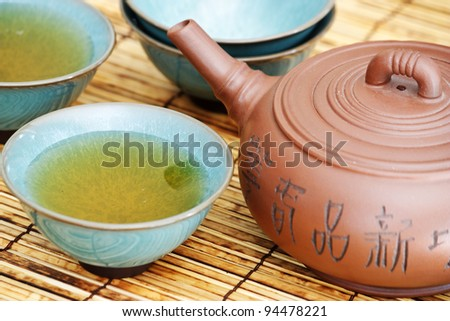 Close up of a asian teapot and few teacups. - stock photo