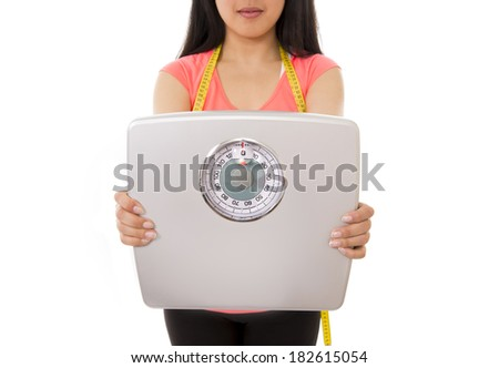 close up of a asian woman holding scales with a tape measure around her neck on a white background - stock photo