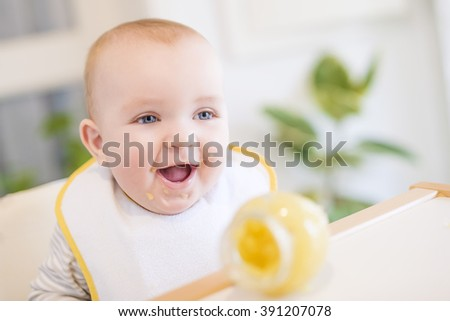 Close up of a baby boy in high chair - stock photo