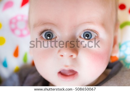 Close up of a baby face with big blue eyes looking wondrous into camera