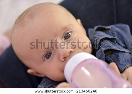 Close-up of a baby girl with beautiful blue eyes bottle feeding  - stock photo