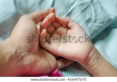 Close-up of a baby hand in father's hand on the blue bed.