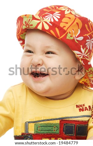 Close up of a baby with two teeth in red panama looking sideways laughing