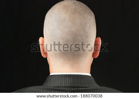 Close-up of a bald suited man, shot from behind. - stock photo