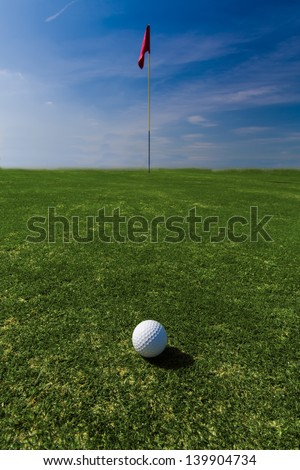 Close up of a ball on a green with a flag in the distance against a blue sky - stock photo