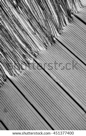 Close up of a barrier made of tree twigs on wooden floor in black and white
