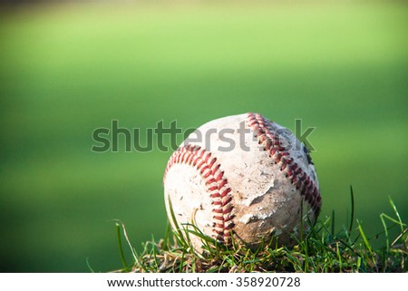 close-up of a baseball in front of a green grass field - stock photo