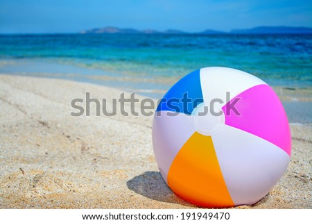 close up of a beach ball by a turquoise shore - stock photo