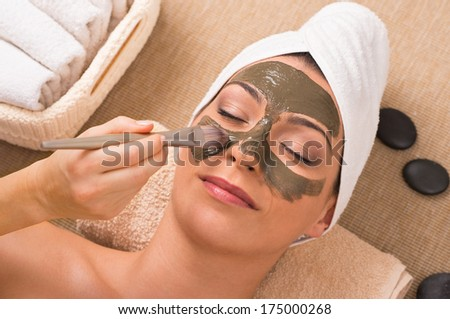 Close Up Of A Beautician Who Apllies The Facial Treatment To a Beautiful Woman In Day Spa - stock photo