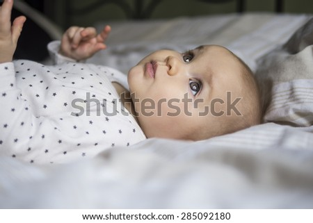 close up of a beautiful baby laying on a bed - stock photo