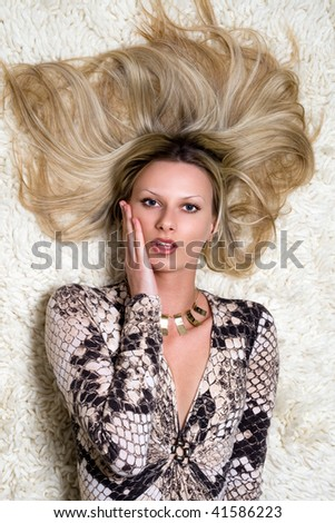 Close-up of a beautiful blond woman lying on the carpet - stock photo