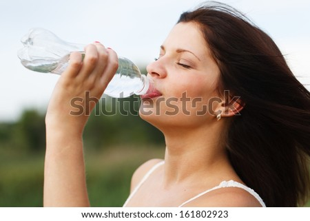 Close-up of a beautiful blonde girl drinking water.