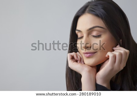 Close-up of a beautiful Indian young woman with eyes closed over colored background - stock photo