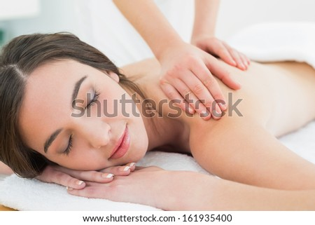 Close up of a beautiful woman enjoying back massage at beauty spa - stock photo