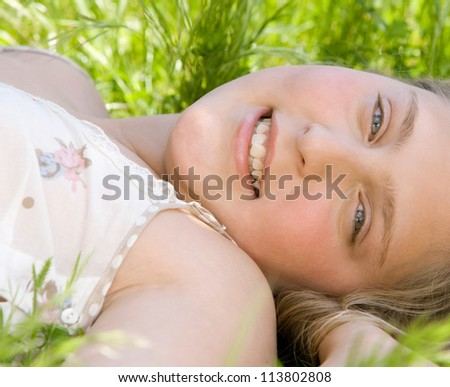 Close up of a beautiful young blond girl laying down on long green grass in a garden while on vacation. - stock photo