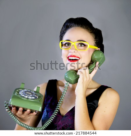 Close up of a beautiful young girl with yellow glasses using an old green phone smiling expression - stock photo