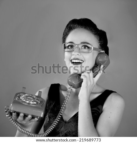 Close up of a beautiful young girl with yellow glasses using an old green phone smiling expression in black and white