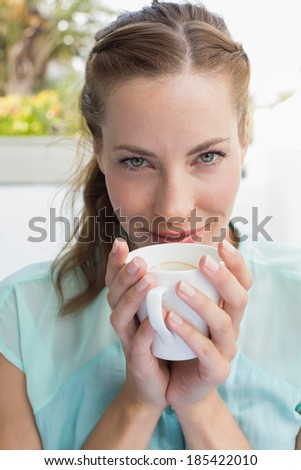 Close-up of a beautiful young woman drinking coffee at the caf�© - stock photo