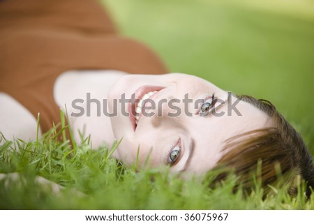 Close-up of a beautiful young woman lying down of grass