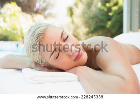 Close up of a beautiful young woman lying on massage table at spa center - stock photo
