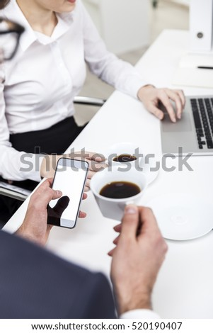 Close up of a bespectacled businessman looking at his smartphone screen and drinking coffee from a white cup. His colleague is typing