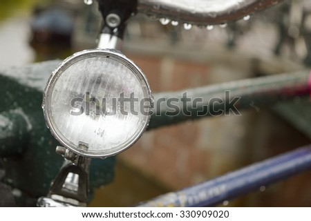 Close up of a bicycle light parked on a bridge in Amsterdam on a rainy day - stock photo