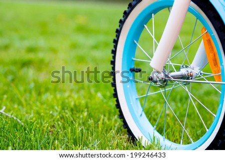 Close up of a bicycle wheel on a green grass field. Outdoors sports concept