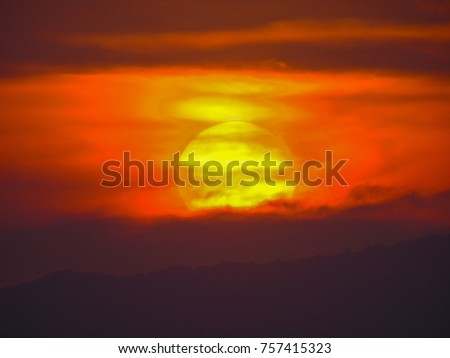 Close up of a big, yellow, setting sun in a red sky over the mountains of Ko Chang, Thailand