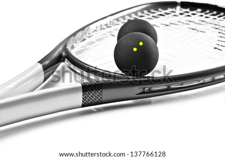Close up of a black and silver squash racket and balls - stock photo